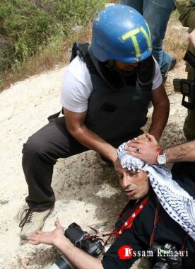 In Case Of Emergency: A journalist provides first aid to the Associated Press photographer Nasser Shiyoukhi after he was hit by a stone in the head near the West Bank city of Ramallah. Photo By Issam Rimawi